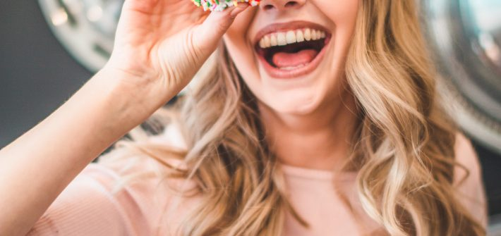 Laughing woman holding a donut | self care ideas