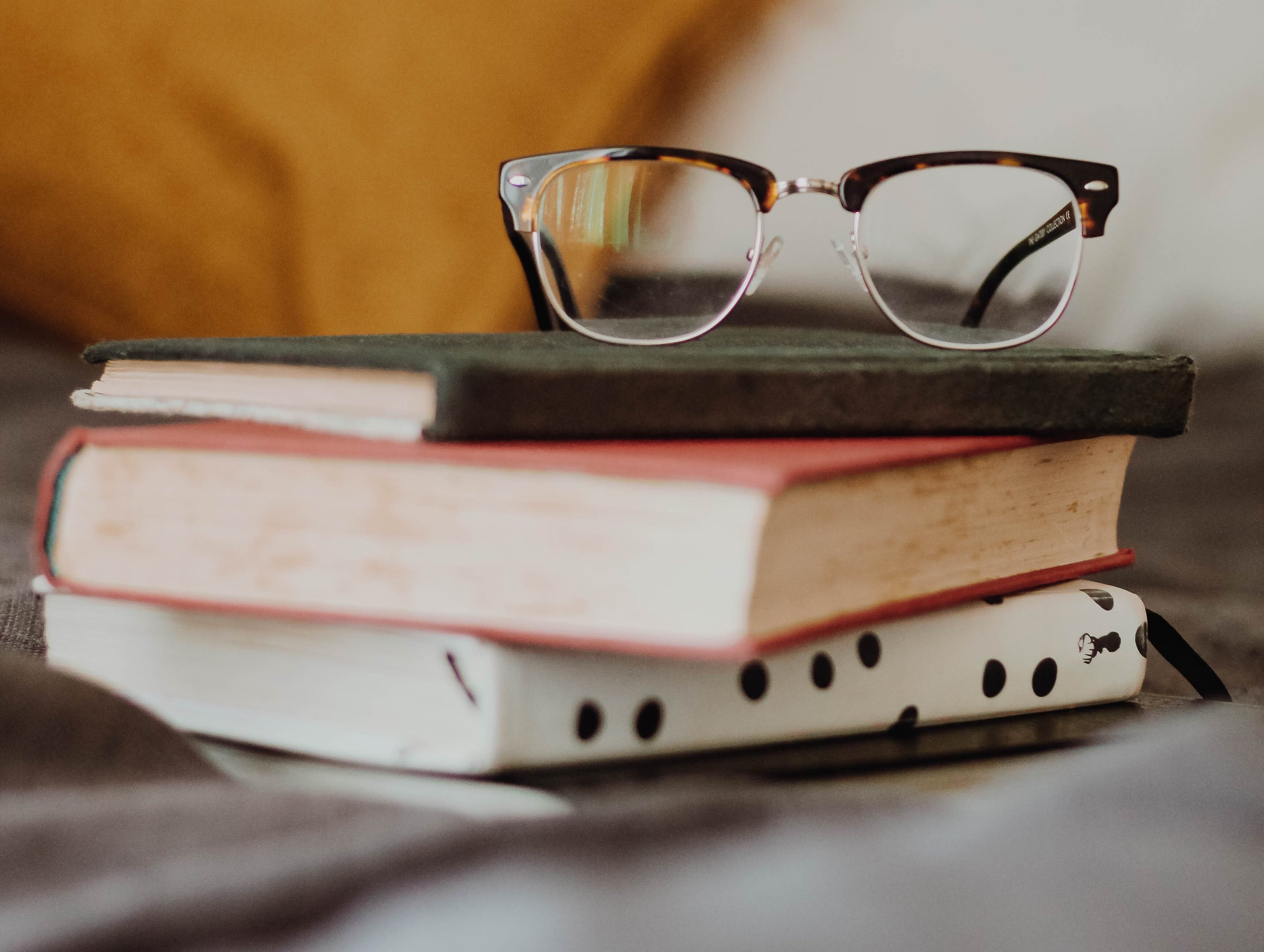 Four books stacked together with reading glasses on top, buy books at the dollar store