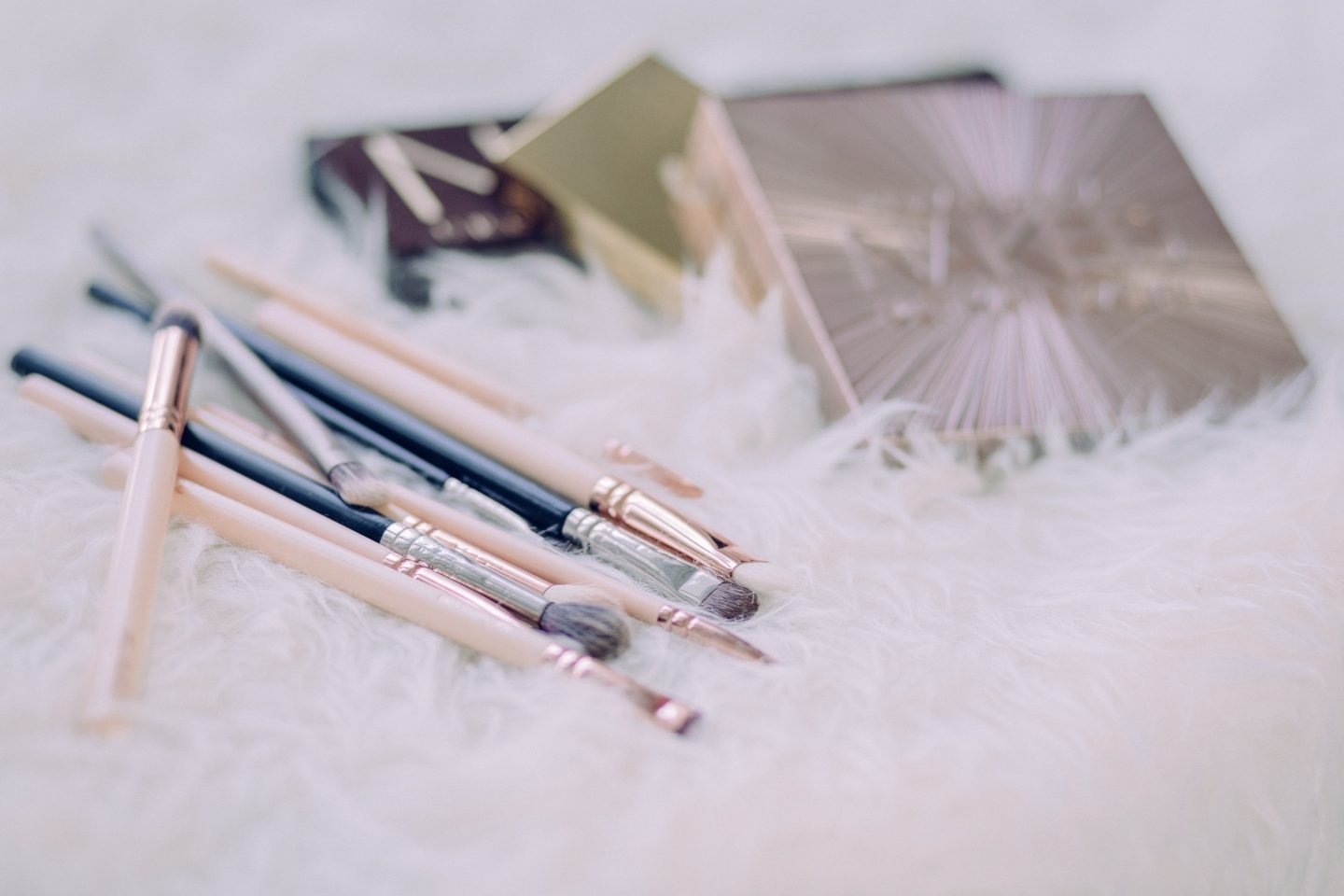 assorted makeup brushes and beauty boxes on white fur