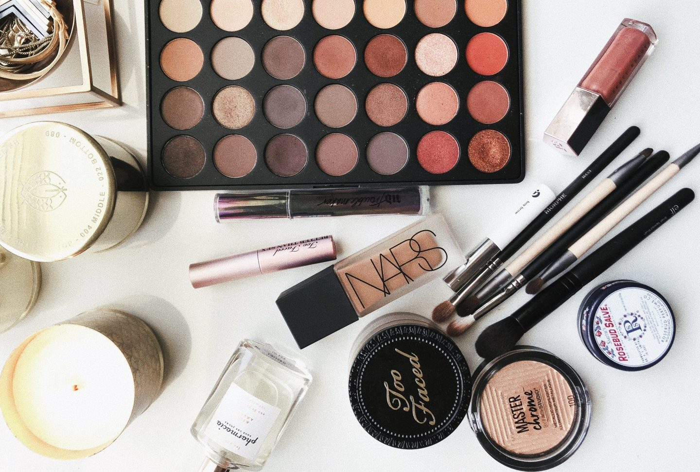 assorted makeup and skincare products on a white background