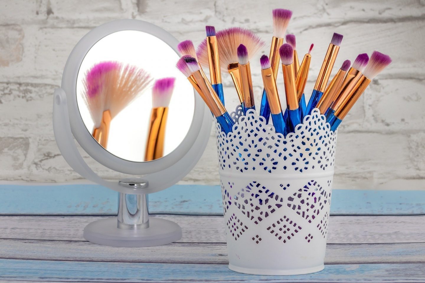 blue makeup brushes in a white container next to round mirror