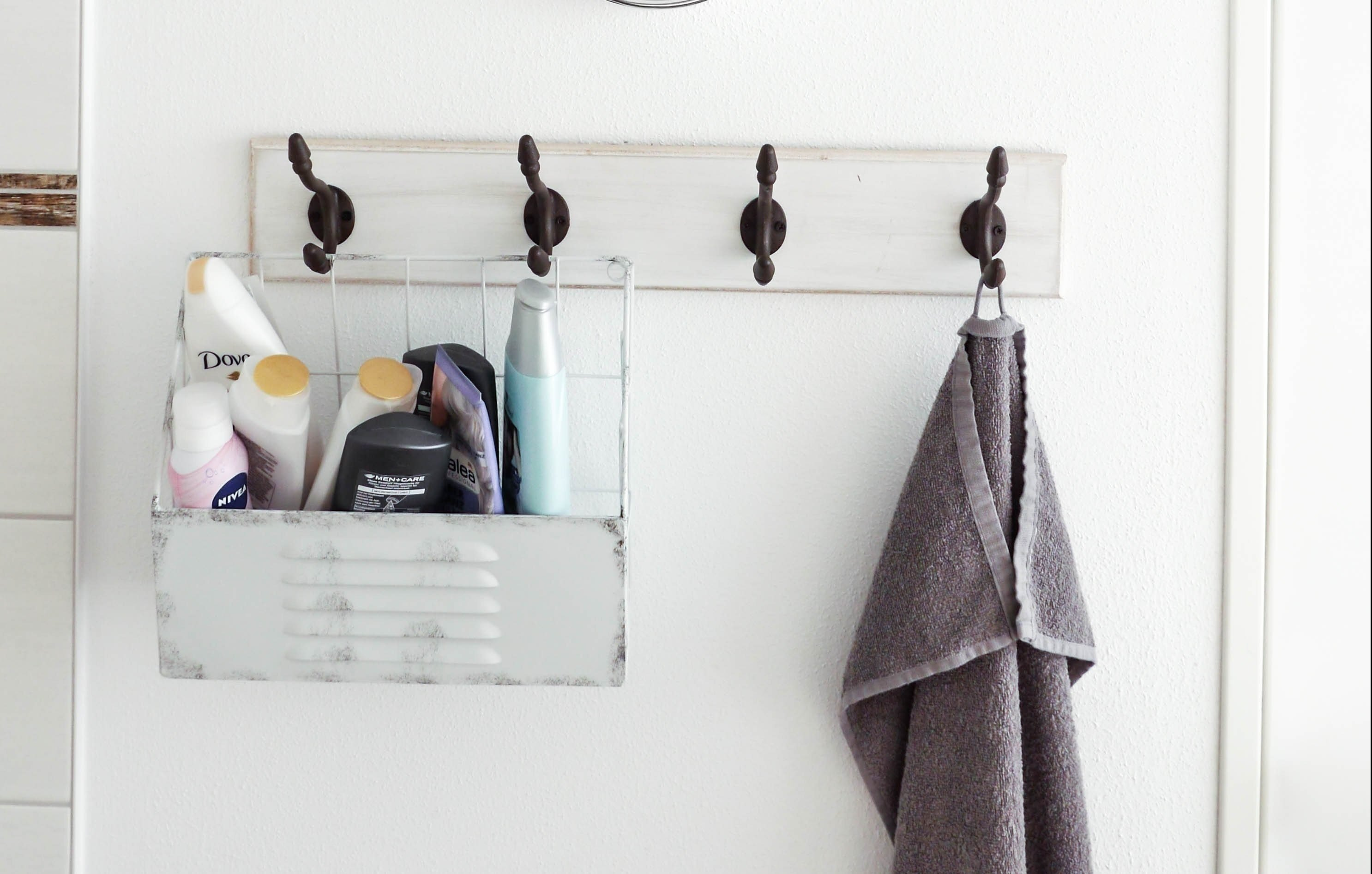 Bathroom wall with hanging towel and shower caddy
